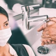 woman wears face mask and man washes hands to prevent coronavirus